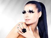 Woman with long black false eyelashes makeup and golden nails — Stock Photo