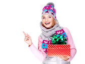 Woman with a gift in a winter outerwear pointing by finger — Stock Photo