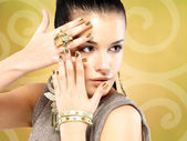Pretty woman with golden nails and beautiful gold ring — Stock Photo