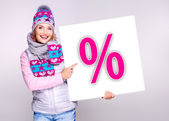 Woman in warm outerwear holds the banner with percent symbol — Stock Photo