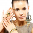 Woman with golden nails and beautiful gold jewelry  — Стоковая фотография