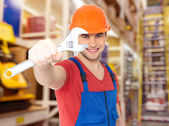 Smiling worker with big spanner — Stockfoto
