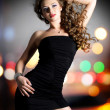 Beautiful woman in black dress poses over night lights — Stock Photo