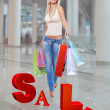 Woman with shopping bags poses at store — Stock Photo #34143285