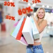 Woman with shopping bags poses at store — Stock Photo