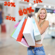 Woman with shopping bags poses at store — Stok fotoğraf