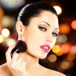 Beautiful woman applying blusher on face — Stok fotoğraf