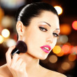 Beautiful woman applying blusher on face — ストック写真