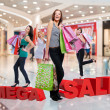 Happy women with shopping bags at store — 图库照片