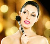 Beautiful woman applying blusher on face — Stock Photo
