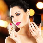 Beautiful woman applying pink lipstick on lips — Stock Photo