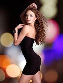 Beautiful woman in black dress poses over night lights — Photo