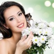 Beautiful woman with clean skin of face with flowers — Stock Photo #34314007