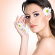 Beautiful woman with clean skin of face with flowers — Stock Photo