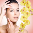 Beautiful woman with clean skin of face with flowers — Stock Photo #34314109