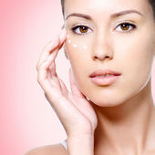 Woman with healthy face applying cosmetic cream under the eyes — Stock Photo