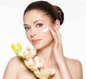Beauty face of woman with cosmetic cream on face — Stock Photo