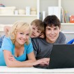 Smiling family using laptop — Stock Photo #3830794