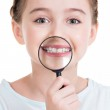 Little girl showing teeth through a magnifying glass — Stock Photo #41927737