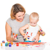 Happy young mother with a baby paint by hands.      — Stockfoto