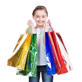 Pretty smiling little girl with shopping bags  — Stockfoto