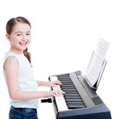 Smiling girl plays on the electric piano. — Stockfoto