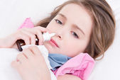 Little girl with bad cold using nasal drops. — Stock Photo