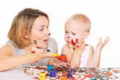 Happy young mother and child with painted hands. — Stock Photo