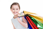 Pretty smiling little girl with shopping bags  — Stock Photo
