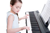 Little girl plays on the electric piano. — Stock Photo