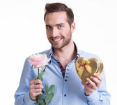 Young happy man with a rose and a gift. — Stockfoto