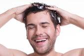 Young happy smiling man washing hair. — Foto de Stock