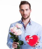 Young man with a pink roses and a gift. — Stock Photo