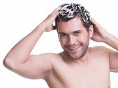 Young happy smiling man washing hair. — Stock Photo
