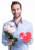Young happy man with a pink roses and a gift. — Stock Photo