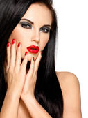 Face of a beautiful woman with red nails and lips — Stock Photo