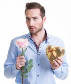 Young man with a rose and a gift. — Photo