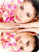 Kadın sağlıklı deri ve pembe çiçek — Stok fotoğraf