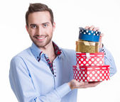 Portrait of happy young man with gifts. — Stockfoto