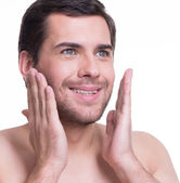 Young handsome man applying lotion. — Stock Photo