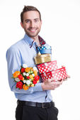 Happy young man with flowers a gift. — Stock Photo