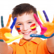 Happy smiling boy with a painted hands and face. — Stock Photo