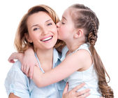 Young daughter  kissing mother — Stock Photo