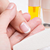 Beautician applying nail varnish on a thumbnail. — Stock Photo
