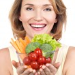 Portrait of a young smiling woman with a plate of vegetables. — Stock Photo