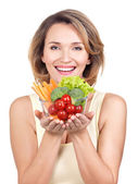 Portrait of a young smiling woman with a plate of vegetables. — Stockfoto