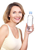 Beautiful young smiling woman with a bottle of wate. — Stock Photo