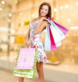 Mulher com sacos de compras na loja — Fotografia Stock
