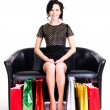 Elegant woman in black dress with shopping bags. — Stock Photo