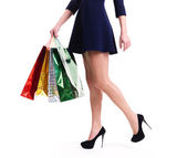 Woman in high heels with color shopping bags. — Stockfoto